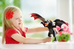 Cute little girl playing with toy dragon at home. Child having fun with big plastic toy. Fantasy and imagination concept Royalty Free Stock Photo