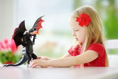 Cute little girl playing with toy dragon at home. Child having fun with big plastic toy. Fantasy and imagination concept Royalty Free Stock Photos