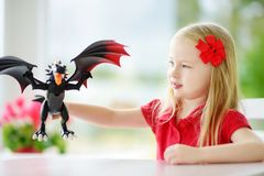 Cute little girl playing with toy dragon at home. Child having fun with big plastic toy. Fantasy and imagination concept Royalty Free Stock Image