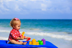 Cute little girl playing with toys on the beach Royalty Free Stock Image