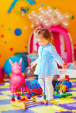 Cute little girl playing with toys in kindergarten Stock Image