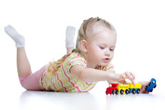 Cute little girl playing trains isolated over white Royalty Free Stock Images