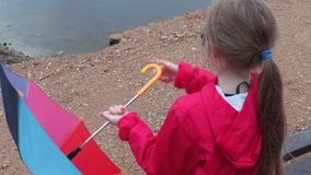 Cute little girl playing with umbrella on bench near lake stock video footage