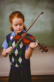 Cute little girl playing violin in classroom Royalty Free Stock Image