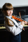 Cute little girl playing violin and exercising indoor stock image