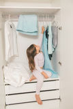 Cute little girl playing in wardrobe Royalty Free Stock Images
