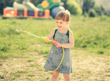 Cute little girl playing water gun Royalty Free Stock Photo