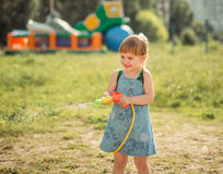 Cute little girl playing water gun Royalty Free Stock Photography
