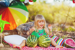 Cute little girl playing with watermelons in summer park outdoors Royalty Free Stock Photos
