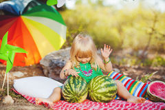 Cute little girl playing with watermelons in summer park outdoors Stock Photography