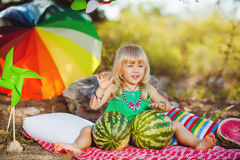 Cute little girl playing with watermelons in summer park outdoors Stock Photos