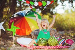 Cute little girl playing with watermelons in summer park outdoors Royalty Free Stock Images