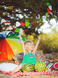 Cute little girl playing with watermelons in summer park outdoors Stock Photo