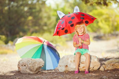 Cute little girl playing with watermelons in summer park outdoors Stock Image