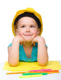 Cute little girl is playing while wearing hard hat Stock Photo