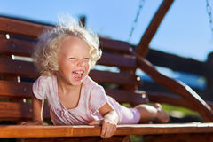 Cute little girl playing on wooden chain s. Cute little girl with blond curly hair playing on wooden chain swing Royalty Free Stock Photos
