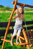 Cute little girl playing on wooden chain swing. Cute little girl with blond long hair playing on wooden chain swing in rural playground Royalty Free Stock Images