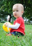 Cute little girl playing with yellow ball Royalty Free Stock Photography