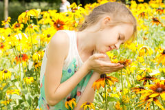 Cute little girl playing with yellow flowers Stock Photos