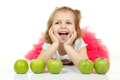 Cute little girl playng with apples and show tongue Royalty Free Stock Image