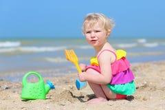 Cute little girl plays on the beach Stock Photo