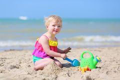 Cute little girl plays on the beach Stock Image