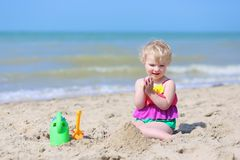 Cute little girl plays on the beach Royalty Free Stock Photo