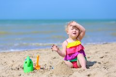 Cute little girl plays on the beach Royalty Free Stock Images