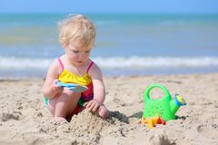 Cute little girl plays on the beach Stock Images