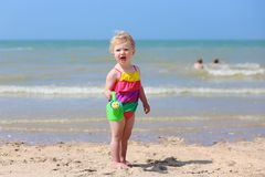 Cute little girl plays on the beach Stock Photos