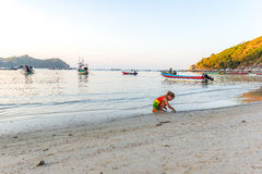 Cute little girl plays on the beach in Thailand royalty free stock image