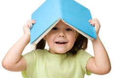 Cute little girl plays with book Stock Photo