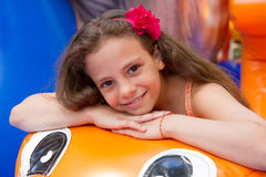 Cute little girl plays in bouncing castle Stock Photos