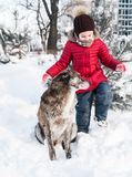 Cute little girl plays with her dog in snow. Cute little girl plays in snow outdoor royalty free stock image