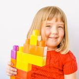 Cute little girl plays with large colorful blocks. Close-up of a cute little girl with blond hair and blue eyes showing off her tower of large colorful plastic Stock Photo