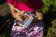 Cute little girl plays with paints. Colors of nature Stock Image