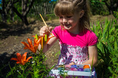 Cute little girl plays with paints. Colors of nature Stock Photo