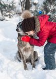 Cute little girl plays with her dog in snow. Cute little girl plays in snow outdoor stock photography
