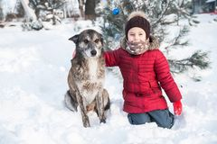 Cute little girl plays with her dog in snow. Cute little girl plays in snow outdoor royalty free stock photography