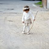 Cute little girl plays with stick Royalty Free Stock Images