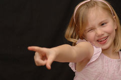 Cute little girl pointing. A cute little 6-year old girl in a pink dress squints her eye and points a finger in the direction of an unseen person or object stock images