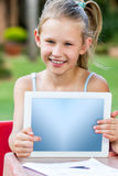Cute little girl pointing at blank tablet outdoors. Close up Portrait of cute teen girl pointing at blank tablet screen outdoors Stock Image