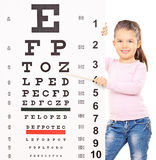 Cute little girl pointing at an eyesight test with stick Royalty Free Stock Photography