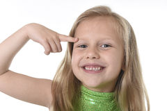 Cute little girl pointing her eyebrow in body parts learning school chart serie. 6 or 7 years old little girl with blond hair and blue eyes smiling happy posing stock photo