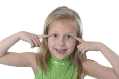 Cute little girl pointing her eyes in body parts learning school chart serie. 6 or 7 years old little girl with blond hair and blue eyes smiling happy posing royalty free stock photos