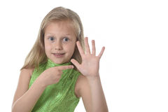 Cute little girl pointing her hand in body parts learning school chart serie. 6 or 7 years old little girl with blond hair and blue eyes smiling happy posing royalty free stock image