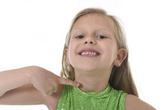 Cute little girl pointing her neck in body parts learning school chart serie. 6 or 7 years old little girl with blond hair and blue eyes smiling happy posing royalty free stock photo