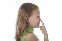 Cute little girl pointing her nose in body parts learning school chart serie. 6 or 7 years old little girl with blond hair and blue eyes smiling happy posing stock image