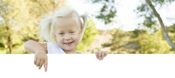 Cute Little Girl Pointing to White Board with Room For Text Royalty Free Stock Photo