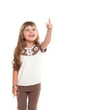 Cute little girl pointing up somewhere and smiling. Cute little girl posing in the studio and point to up somewhere against white background Royalty Free Stock Photography